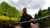 Male tourist kayaking on river, action camera, vacation, slow-mo video