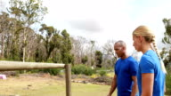 Male trainer assisting woman to climb a hurdles during obstacle course video
