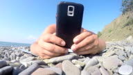 Male traveler holding smart phone in hands lying on the beach close up video