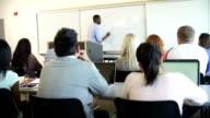 Male Tutor Teaching University Students In Classroom video