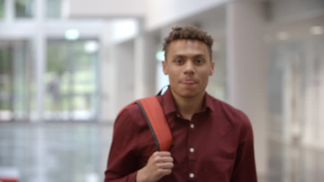Male university student walking into focus in a modern lobby video