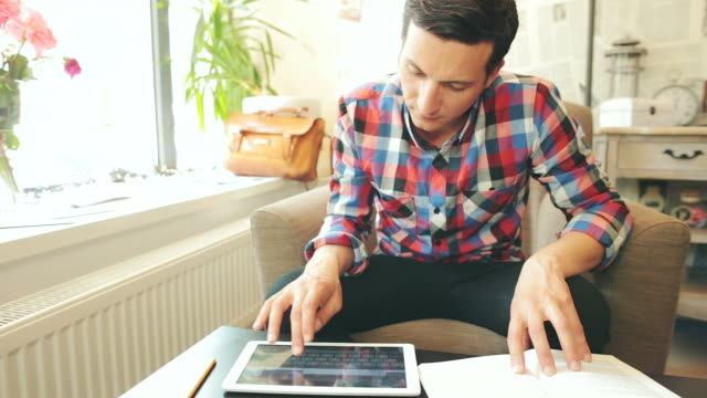 Male using a digital tablet and reading a book. video