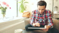 Male using a digital tablet in coffee shop. video
