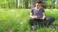 Male using a digital tablet in park. video