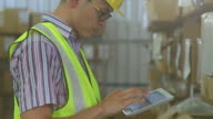 Male using digital tablet in warehouse video