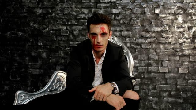 Male vampire sitting on a black sofa video