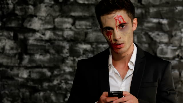 Male vampire uses a smartphone video