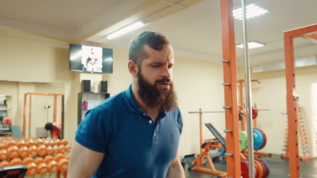 Male with beard does on the exercise machine video
