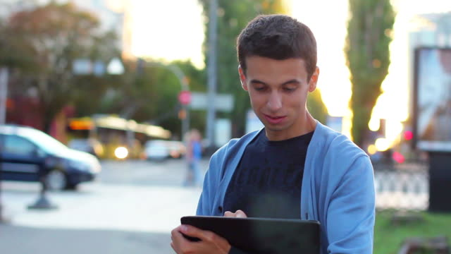 Male with tablet computer smiles, inspire ideas thinking looking video