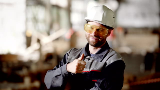 Male worker on construction. Man wearing uniform and glasses posing with hands crossed on background of site video