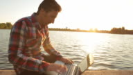 Male working at his laptop in nature at sunset. video