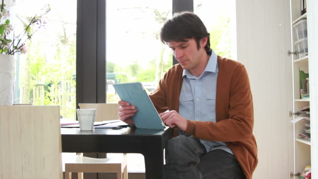Male working from home on digital tablet video