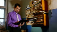 man accounting clerk retro touches the paper in an old office video