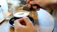 Man adding sugar into coffee at coffee shop video