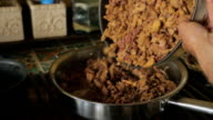 A man adds chopped liver to a frying pan on a stovetop in slow motion video