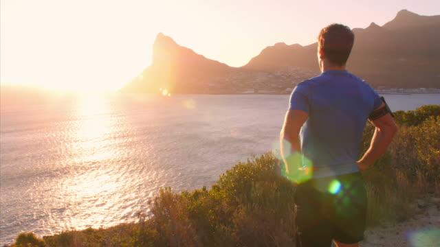 Man admiring a coastal view after jogging video