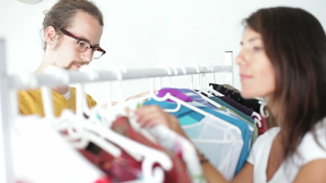 Man & woman shopping fighting over clothes video