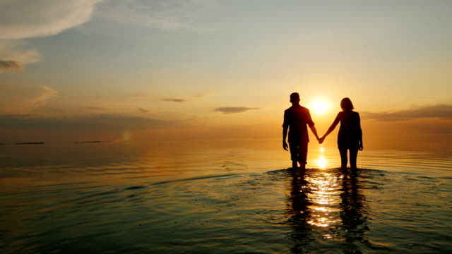 A man and a woman go to the sea at sunset, holding hands. Silhouettes in the light of the setting sun video