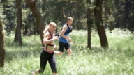 SLO MO DS Man and woman running marathon through forest video