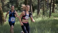 SLO MO DS A man and a woman running a trail marathon through the forest video