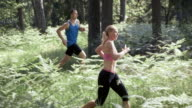 SLO MO DS Man and woman running in forest video