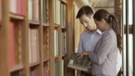 TU Man and woman thumbing through a book in library video
