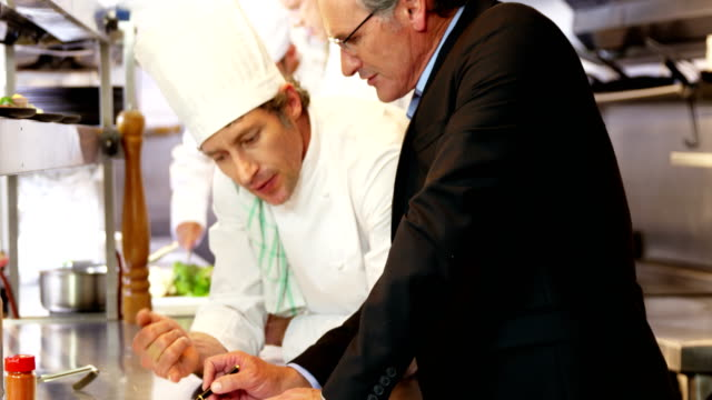 Man and chef looking at a clipboard video