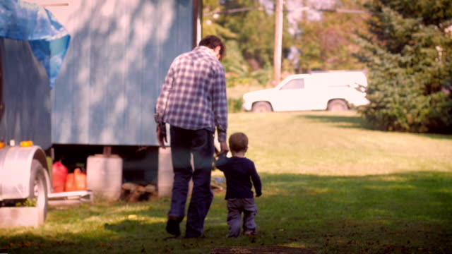 Man and child holding hands and walking away together video