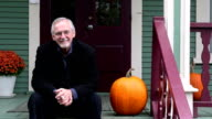 Man and pumpkin sitting on a country porch smiling video