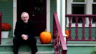 Man and pumpkin sitting on a country porch video