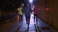 TS Man and two women running in city at night video