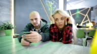 Man and woman at a table in a cafe. Girl with blond hair talking animatedly on the phone. she had an important conversation. Bald man played on his phone video