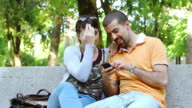 HD: Man and Woman at Park Looking Mobile Phone video