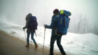 Man and woman backpackers enjoying on foggy forest mountain trail video