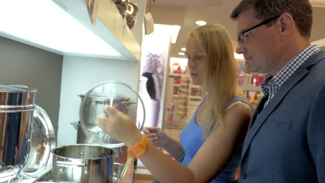 Man and woman buying metal cooking pot in the store video