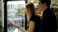 Man and woman buying prepack in frozen section video