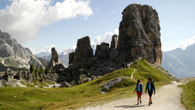 Man and woman couple hiking along Cinque Torri trail path. Group of friends summer adventure journey in mountain nature outdoors. Travel exploring Alps, Dolomites, Italy. 4k slow motion 60p video wide video
