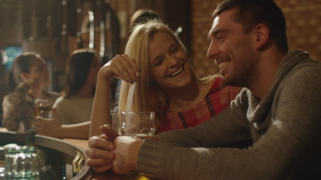 Man and woman couple laugh, drink and have good time in a bar. video