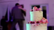 Man and woman dancing at background of beautiful wedding cake decorated with natural roses blooms and berries close up. Banquet reception arrangement and catering. Floral decoration in culinary video