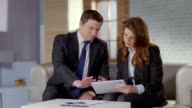 Man and woman discussing business matters in office, slow motion video