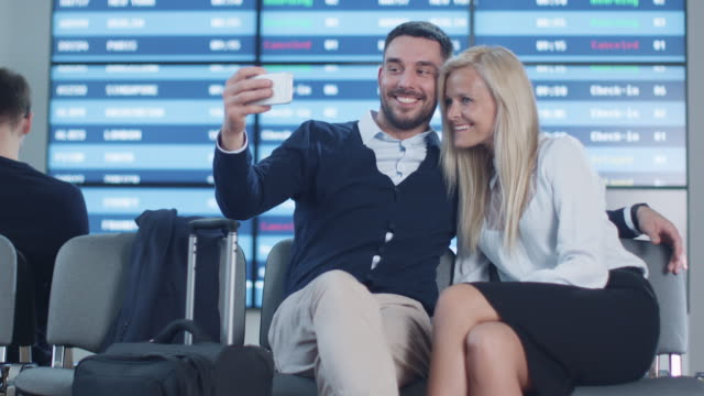 Man and Woman do Selfie Pictures with Phone while Waiting Boarding at Departure Lounge at the Airport. video