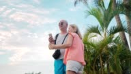 man and woman doing selfie at sunset on the island paradise video