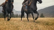 SLO MO Man and woman galloping on horses across meadow video