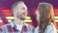 Man and Woman Happy Chatting Purple Colored Bright Lights Spinning Background video