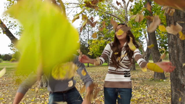 Man and woman have fun throwing leaves in fall video