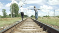 Man and woman holding hands walking along railway video