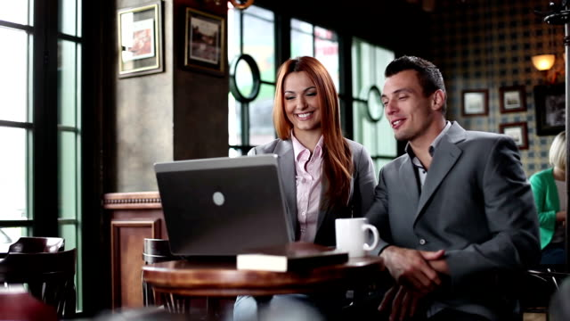 Man and woman in cafe using laptop. video