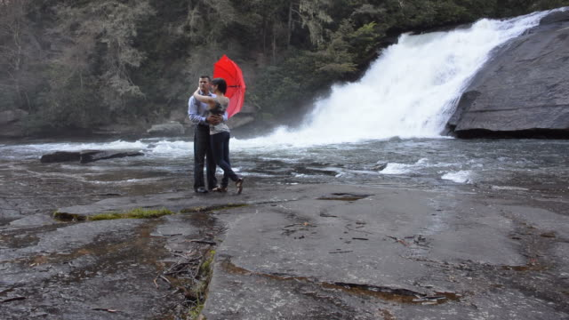 Man and woman in front of waterfall holding each other video