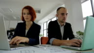man and woman in suits sitting in a large bright spacious office and working together on one project video