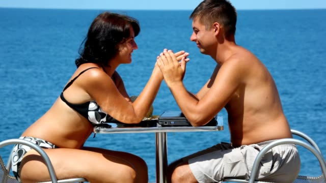 Man and woman in swimsuit sits at table video